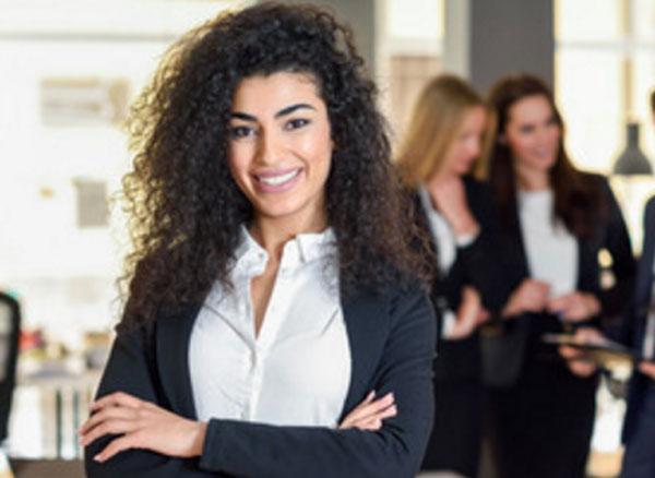 Девушка с кучерявыми волосами улыбается. Она ан работе в офисе