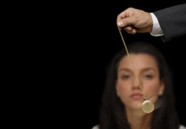Женщина,перед глазами которой мужчина двигает часами на цепочке, совершая маятникообразные движения
