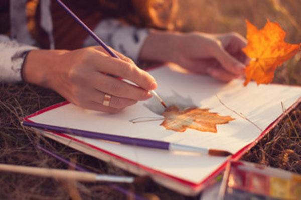 Женщина держит в руке кленовый листик и рисует его гуашью на бумаге
