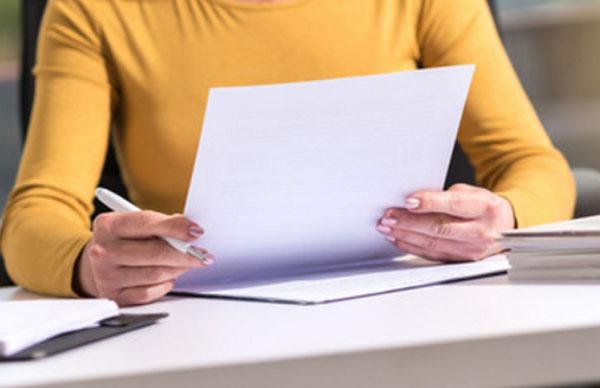 Женщина держит листок бумаги и ручку