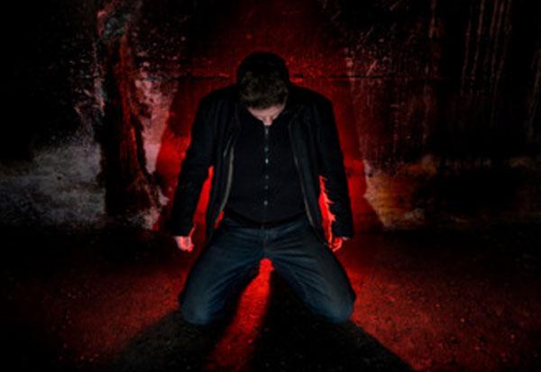 Мужчина стоит на коленях с опущенной головой