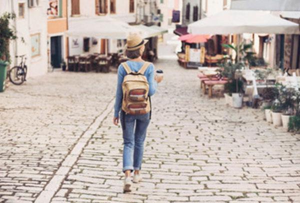 Женщина в шляпе и с рюкзаком идет по улице