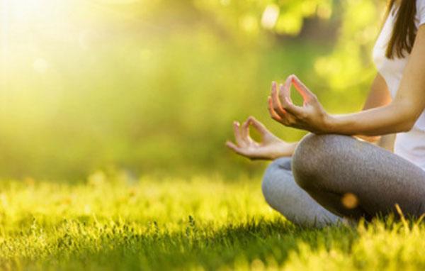 Женщина занимается медитацией, сидя на траве