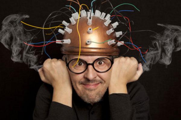 Мужчина со шлемом на голове, из которого торчат провода и из ушей идет дым