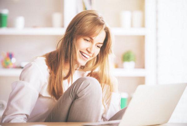 Девушка смотрит на экран ноутбука и смеется