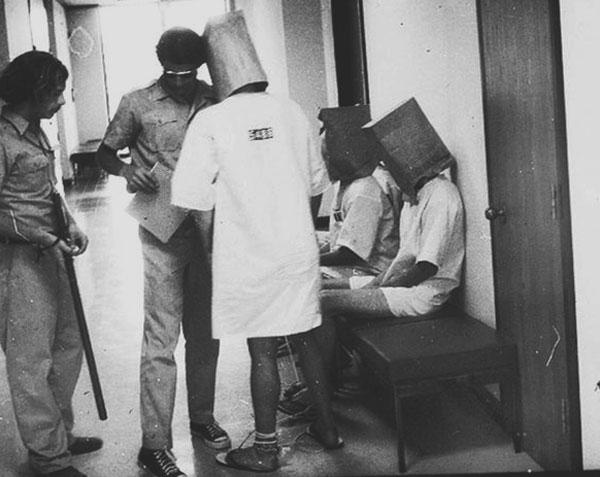 """Фотография, на которой изображены """"надзиратели"""" и """"заключенные"""" с коробками на голове"""