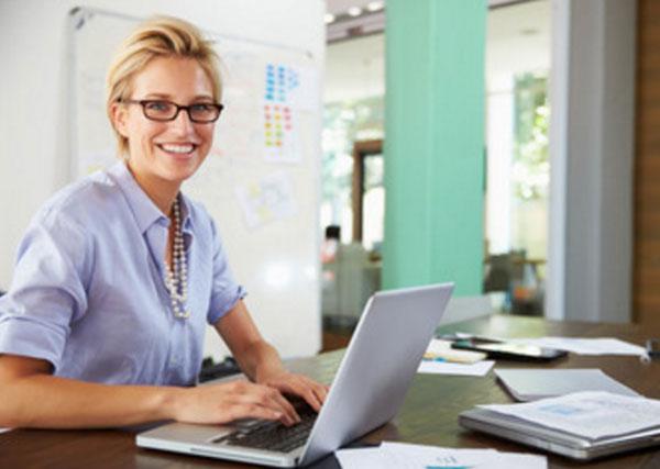Улыбчивая женщина сидит за ноутбуком