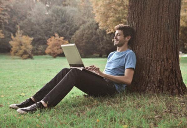 Парень сидит под деревом и что-то печатает на ноутбуке