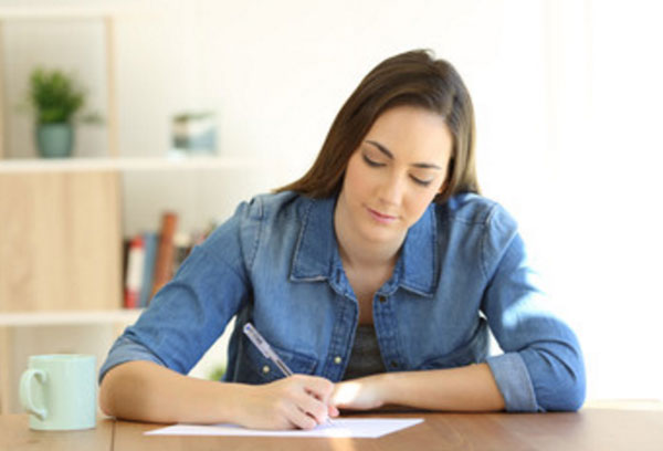 Женщина что-то пишет на листке бумаги