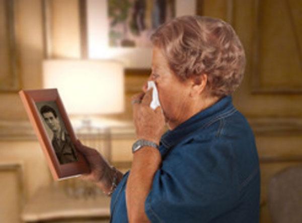 Пожилая женщина плачет, глядя на старое фото