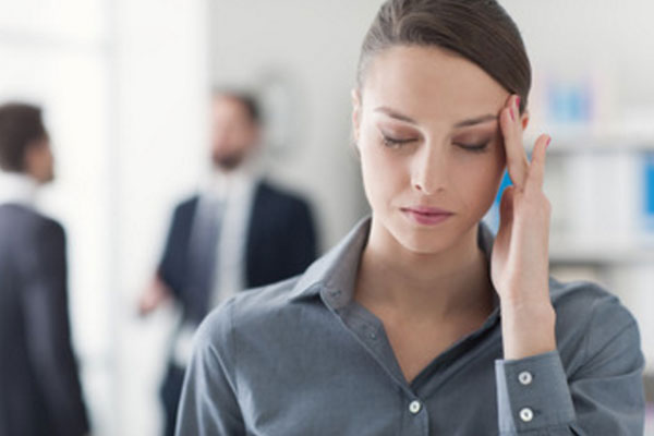 Женщина с закрытыми глазами держится за висок