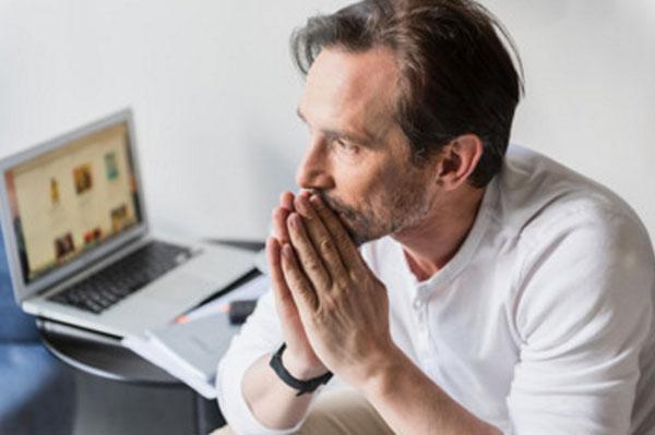 Расстроенный мужчина сидит возле включенного ноутбука