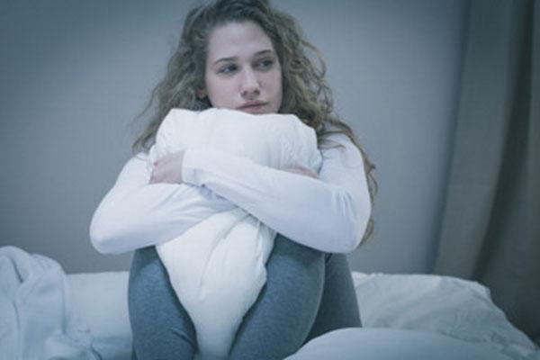 Грустная девушка сидит в обнимку с подушкой