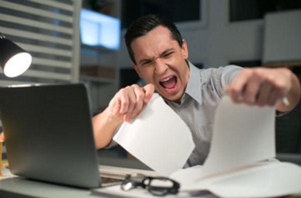 Мужчина в нервном напряжении рвет листы бумаги