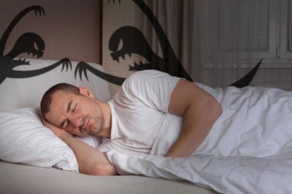 Мужчина спит. На его лице тревога. Сзади него силуэты двух монстров
