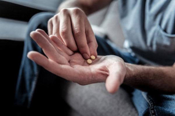 Ладонь мужчины, на которой лежит две таблетки