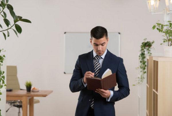 Мужчина в костюме стоит, читая книгу