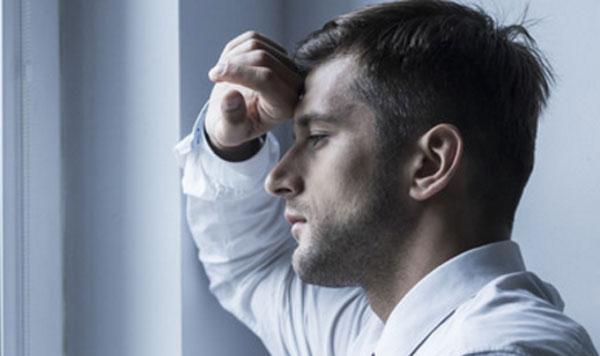 Мужчина стоит у окна, куда-то печально глядит