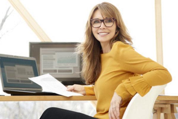 Счастливая женщина сидит на рабочем месте