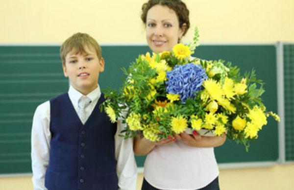 Учительница держит букет цветов. рядом стоит мальчик-подросток