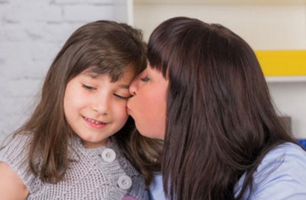 Мама целует смущенную дочку