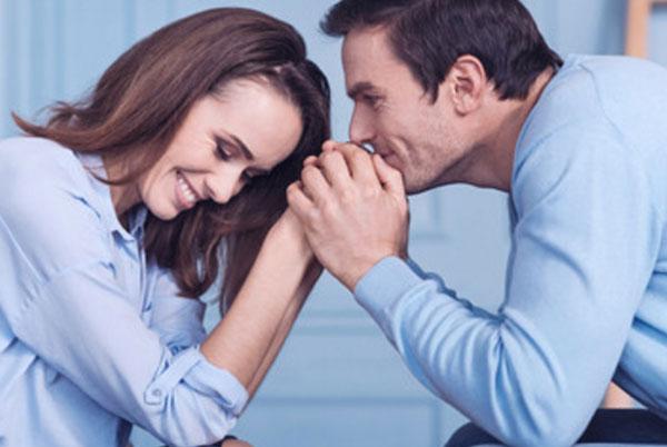 Мужчина и женщина сидят друг напротив друга. Мужчина держит женские руки в своих руках. Женщина смущенно улыбается