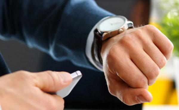 Мужчина смотрит на наручные часы. В руке держит мобильный телефон
