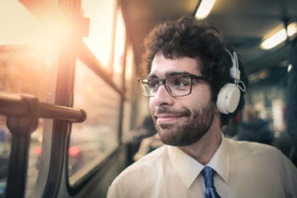Счастливый мужчина едет в транспорте, слушает музыку в наушниках