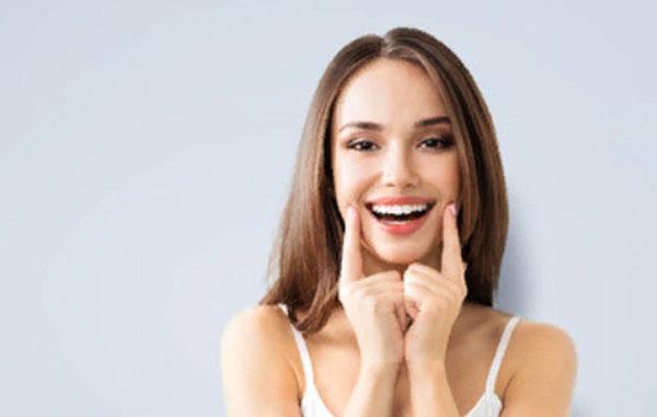 Девушка пальцами касается краев своей улыбки