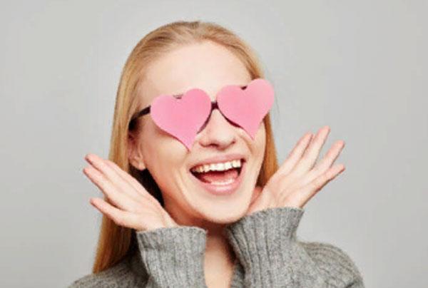 Счастливая девушка смеется. На ней очки в виде сердец