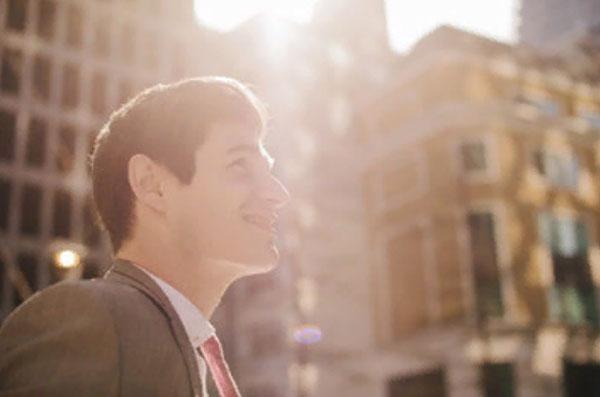 Улыбающийся мужчина идет по улице. Светит солнце