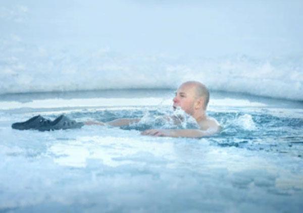 Замерзший мужчина в ледяной воде