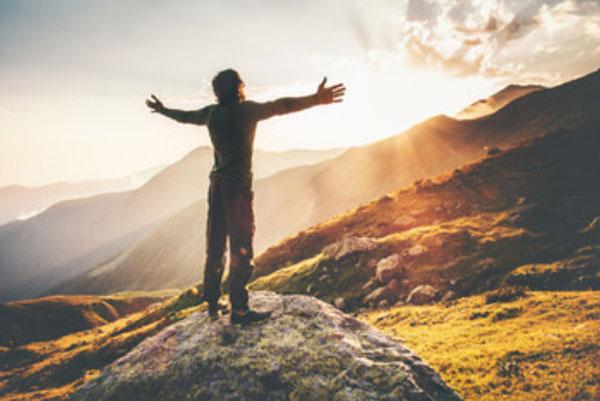 Мужчина стоит на склоне горы с распростертыми руками