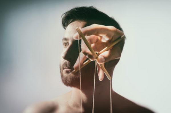 Голова мужчина, на фоне которой видна рука с ниточками для марионетки