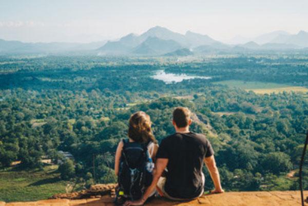 Парень с девушкой сидят на склоне. Перед ними открывается красивый пейзаж