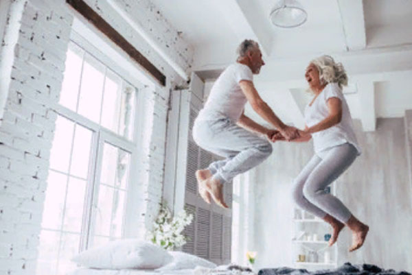 Мужчина и женщина пенсионного возраста прыгают на постели, как молодые