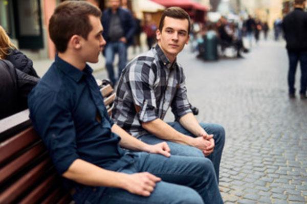 Два парня сидят на скамейке