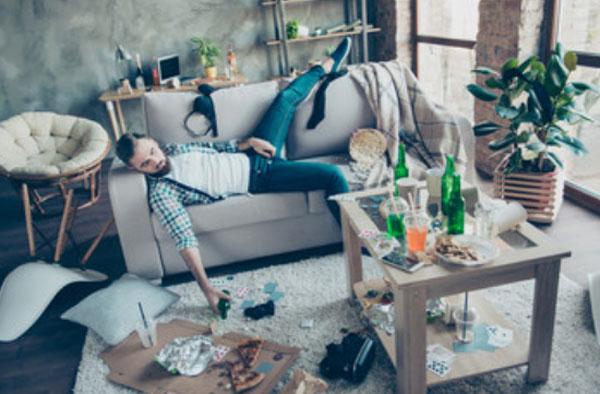 Мужчина лежит на диване. В комнате полный беспорядок