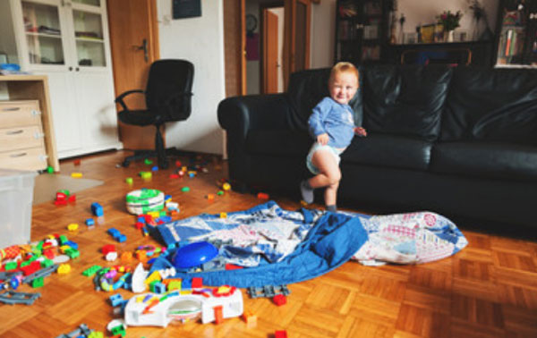 Маленький мальчик стоит посреди комнаты, в которой разбросаны игрушки