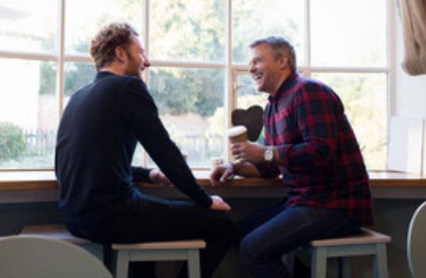 Два мужчины сидят за барной стойкой