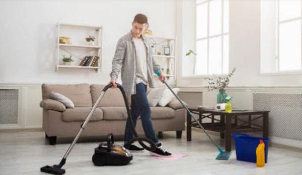 Мужчина пылесосит комнату