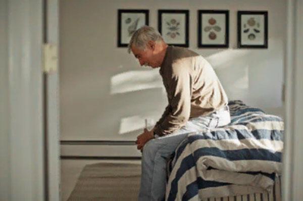 Подавленный мужчина сидит на кровати
