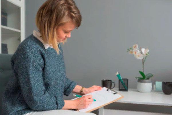 Женщина сидит за столом и что-то пишет