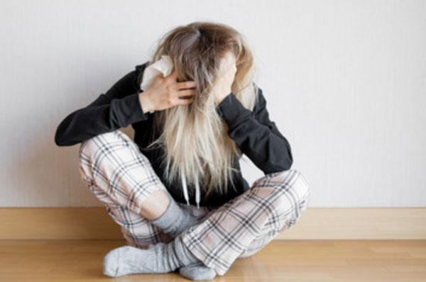 Женщина сидит на полу под стенкой. Она держится за голову