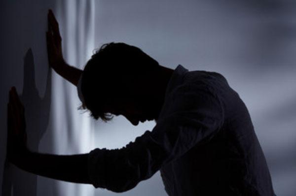 Силуэт мужчины в темноте, который облокотился на стену