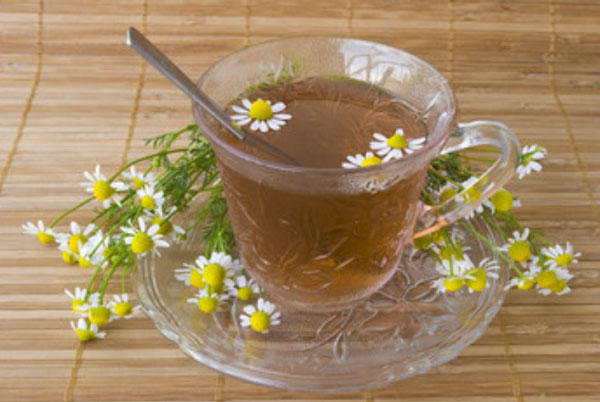 Чашка чая. Рядом лежат ромашки