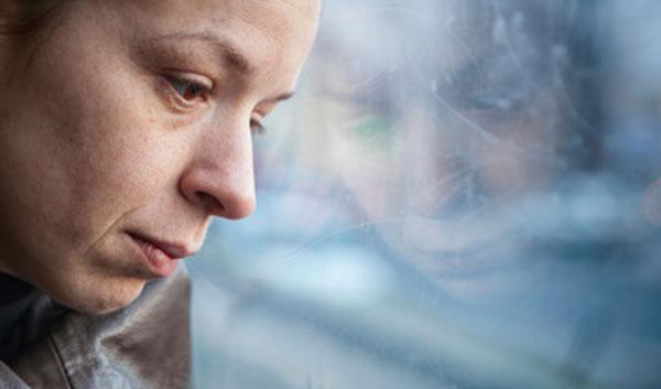 Женщина с отрешенным взглядом облокотила голову на стекло окна