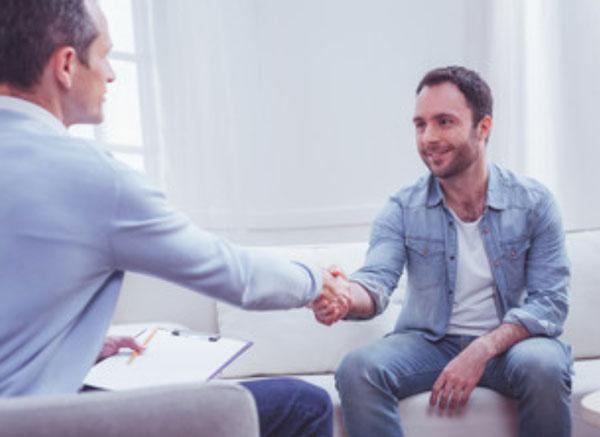 Счастливый мужчина пожимает руку психотерапевту