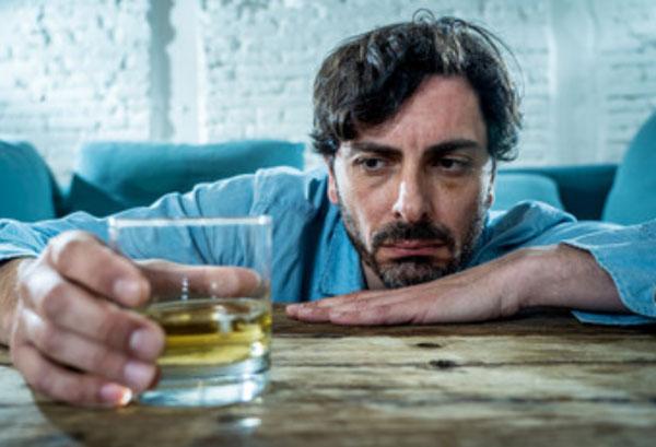 Мужчина держит в руке стакан со спиртным. Томно на него смотрит