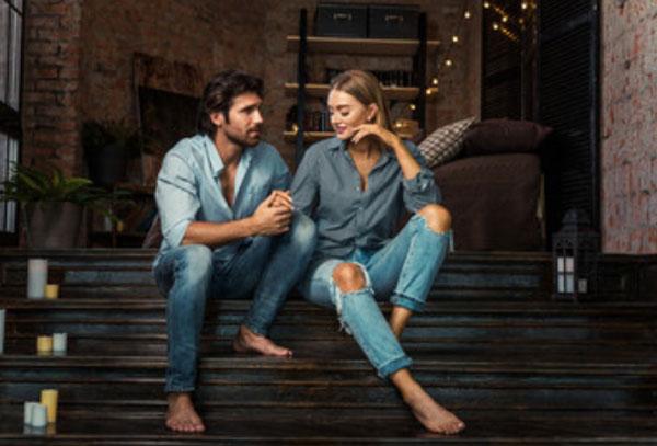 Парень с девушкой сидят на ступеньках. Он что-то говорит